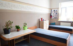 Pokój w internacie z dwoma łóżkami i stolikiem