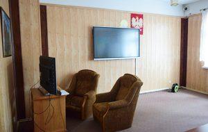 Pokój świetlicy z dwoma fotelami i dwoma telewizorami