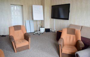 Pokój świetlicy z dwoma fotelami, kanapą oraz telewizorem