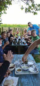 Wychowankowie jedzący wspólny posiłek na świeżym powietrzu