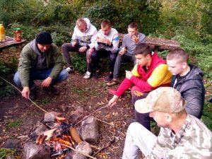 Wychowankowie pieczący kiełbaski koło ogniska