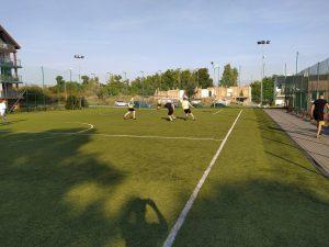 Wychowankowie i pracownicy na boisku grający w piłkę nożną