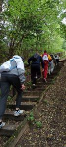 Wychowankowie wchodzą po drewnianych schodach na szlaku